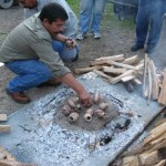 Placing the pots on the wire screen on a bed of coals
